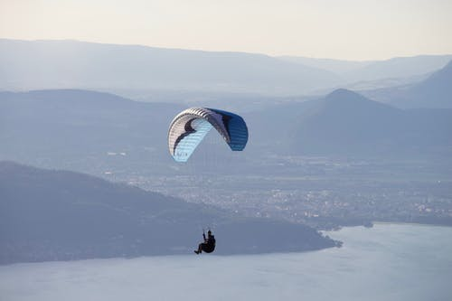 Unrecognizable person flying paraglider with blue parachute above calm water near mountains with settlement in distance against cloudless sky in nature