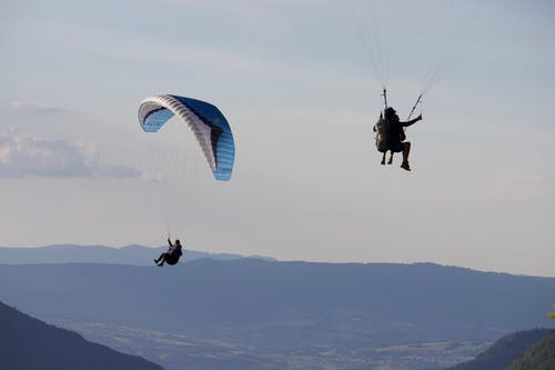 Unrecognizable people flying paragliders above mountains