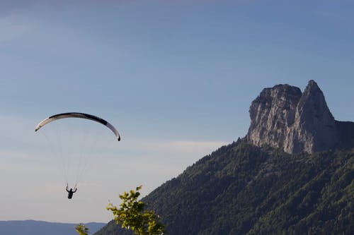Anonymous person flying paraglider with parachute near rocky cliff covered with grass above mountainous area in daylight in nature outside
