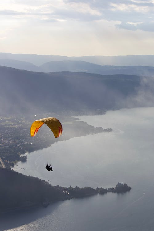 Paraglider flying over river in mountains