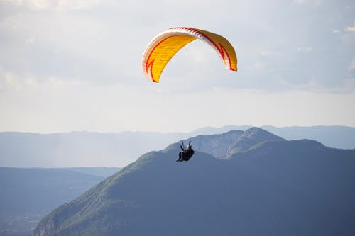 Anonymous paraglider flying over mountains in nature