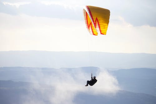 Unrecognizable person flying paraglider with yellow parachute over mountainous terrain against cloudy sky in nature in misty weather during training