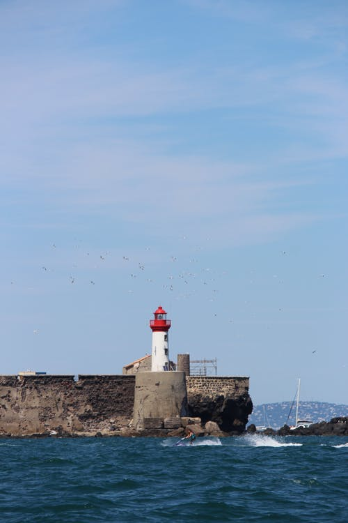 Distant white lighthouse with red tower located on stony pier near rippling sea against blue sky in nature in coastal area