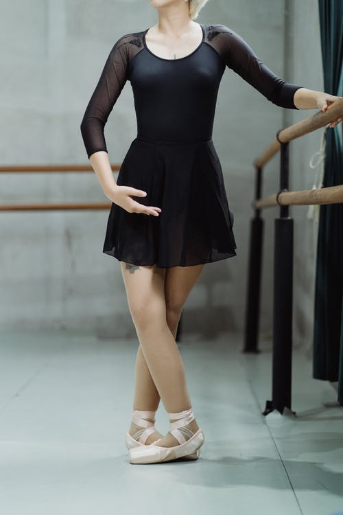 Crop unrecognizable ballerina in black dress and pointe shoes practicing dance movements near barre in modern dance studio