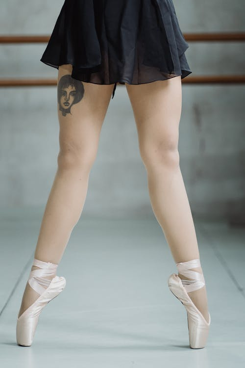 Crop faceless ballerina tiptoeing on pointe shoes in studio