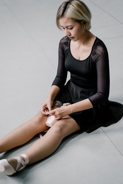 Corte A Bailarina Sentada No Chão Com Sapatilhas De Ponta Nas Mãos