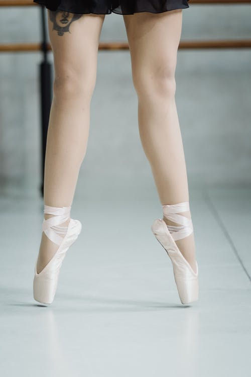 Crop faceless ballerina tiptoeing in ballet school