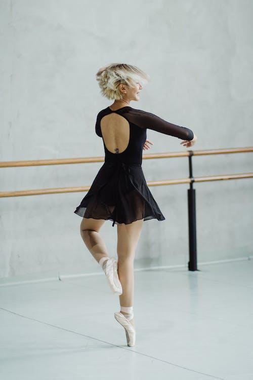 Smiling female dancer doing ballet move