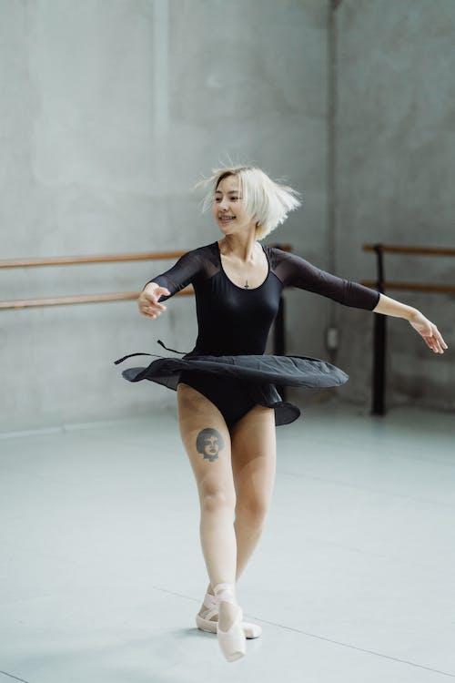 Full length of active graceful female ballet dancer doing spin in empty studio
