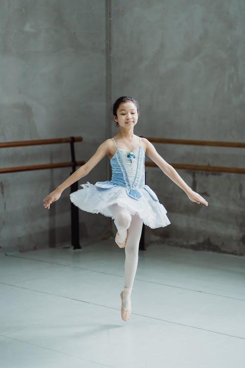 Graceful ballerina jumping on tiptoes in ballet class