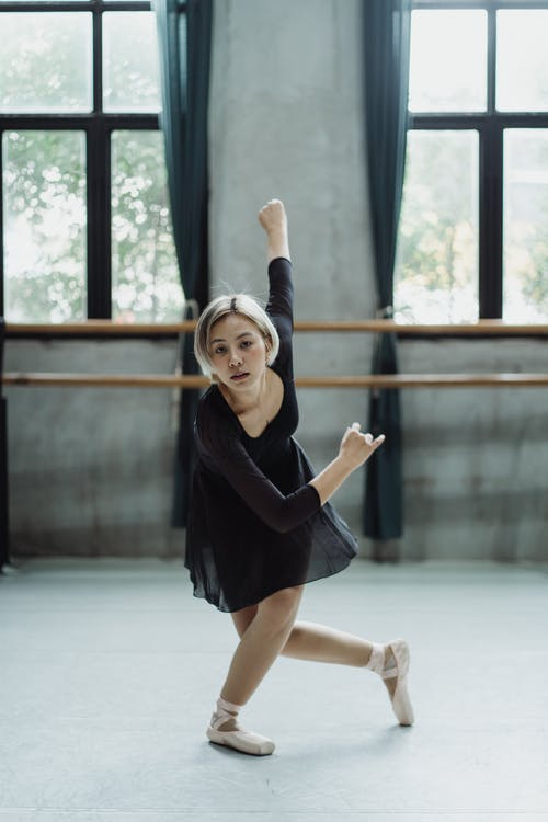 Full length of ethnic ballerina doing ballet move while rehearsing in dance studio
