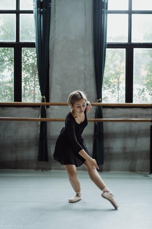 Full length of focused female dressed in black leotard and pointe performing ballet dance in studio