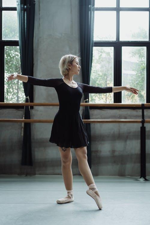 Graceful ballerina staying in ballet room near barre