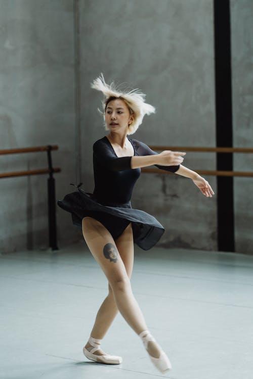 Asian ballerina with flying hair dancing in studio