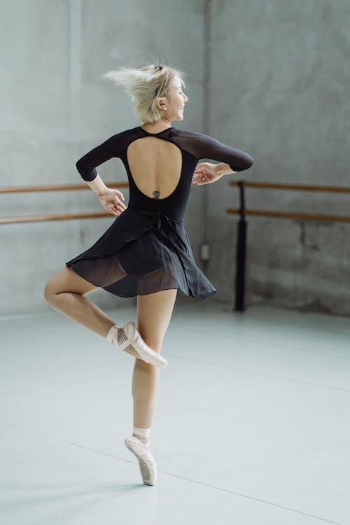 Full length back view of female dancer spinning on tiptoes in ballet school