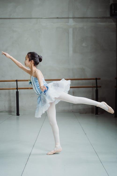 Graceful ballerina practicing Arabesque balance exercise in ballet studio