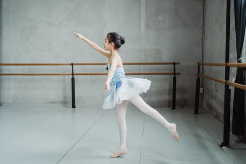 Side view full body of little ballerina practicing Arabesque position while training skills in dancing school