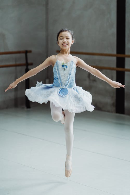 Full body of little cheerful girl with toothy smile in tutu performing ballet dancing in studio