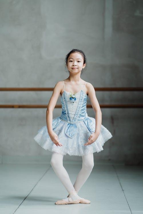 Smiling Asian ballerina girl performing plie in ballet school