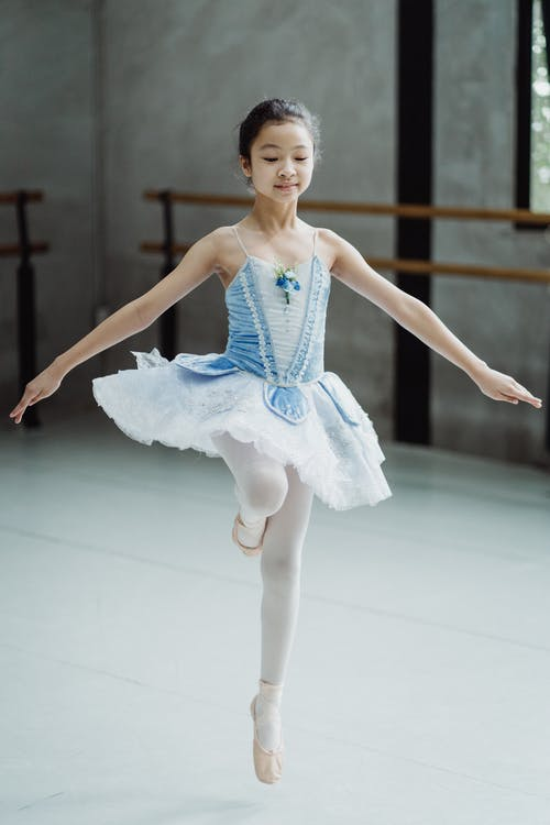 Full body dedicated Asian ballerina girl in blue tutu skirt jumping graciously and performing dance while practicing in ballet school