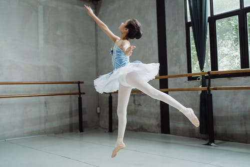 Ballerina girl performing ballet jump in studio