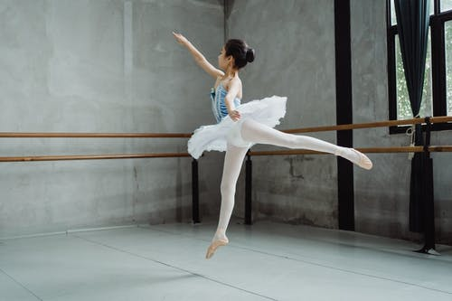 Side view full body ballerina girl wearing white tutu skirt performing ballet jump while exercising in spacious light ballet school
