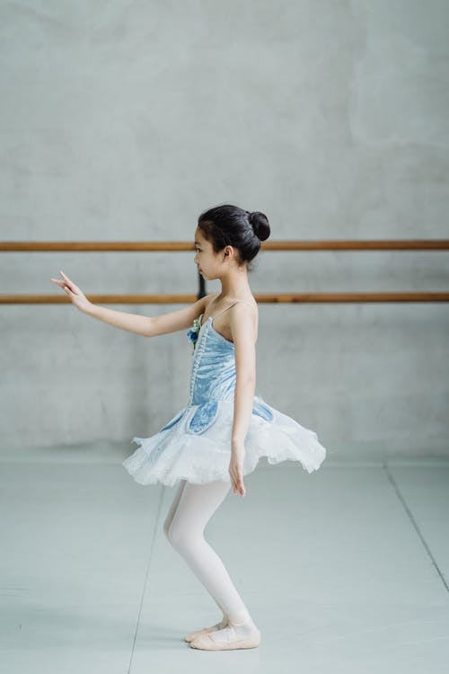 Full body side view of ballerina in tutu and pointe rehearsing dance in ballet studio