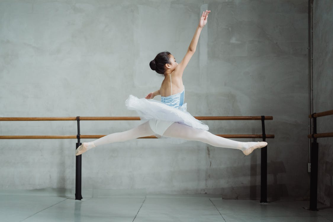 Graceful ballerina doing twine jump in studio