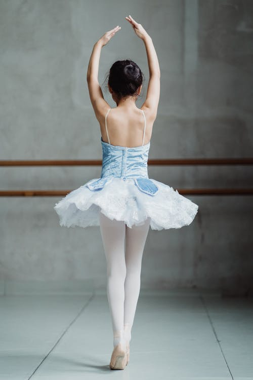 Ballet dancer on tiptoes with hands up
