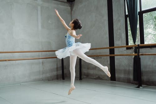 Full body of graceful ballet artist jumping above ground while dancing in choreography hall