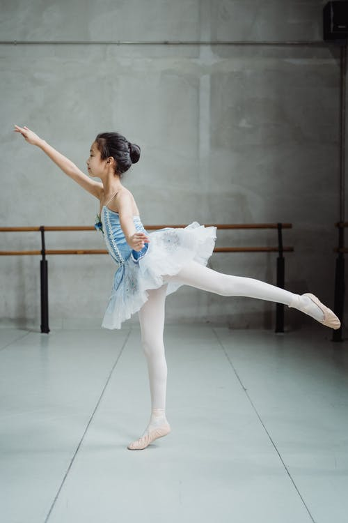 Ballerina stretching body in ballet studio