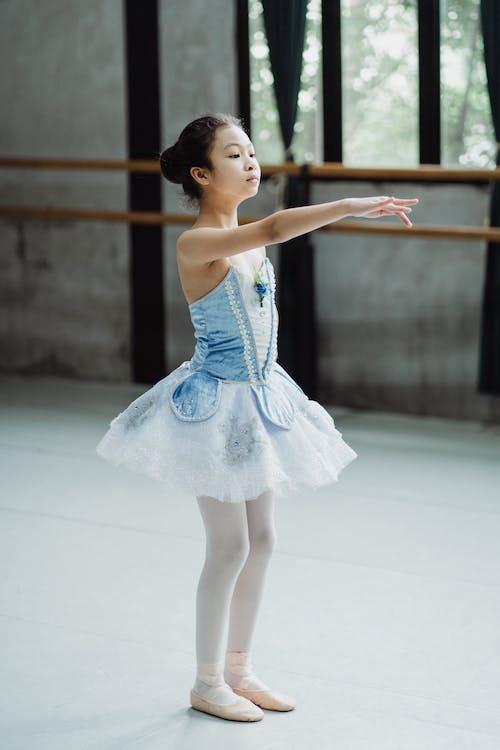 Full body side view of Asian ballerina in tutu skirt doing graceful movement in dance studio