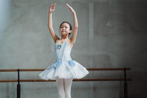 Graceful ethnic little ballerina dancing in studio