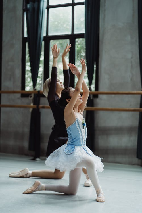 Graceful girl learning ballet dance with trainer