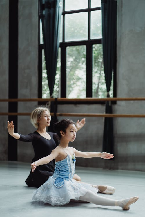 Full body side of ethnic little girl wearing tutu stretching legs with arms outstretched on floor with female instructor in ballet studio