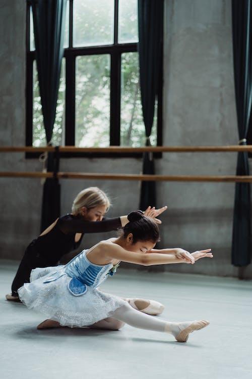 Graceful Asian girl practicing ballet with ballerina in studio
