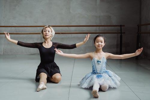 Full body of ethnic ballerinas practicing skills on floor in ballet studio during lesson