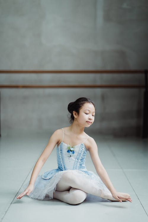 Graceful ethnic ballet artist practicing in dance studio