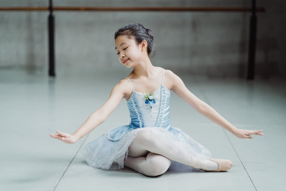 Little ethnic charming ballerina sitting on floor in ballet studio