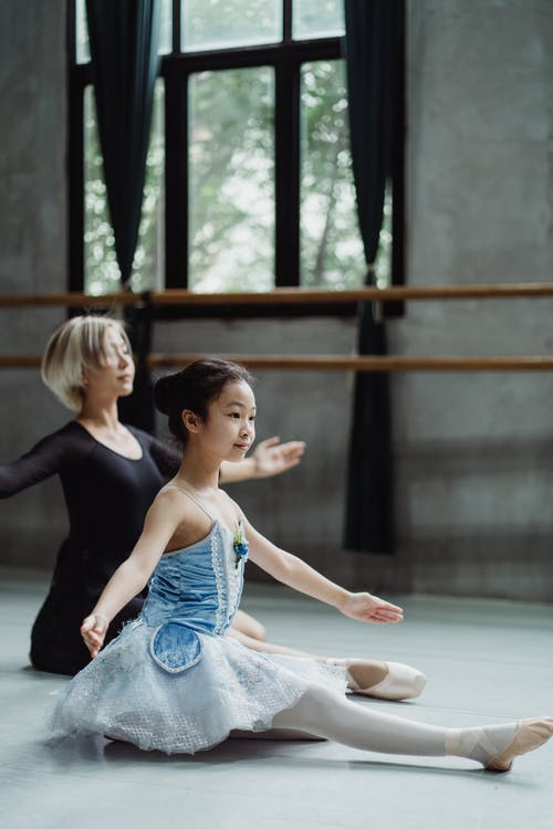 Full body side view of small Asian positive ballet artist practicing dance in studio with barre