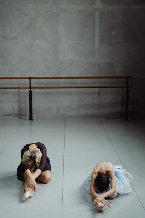 Ballet dancers stretching body in studio