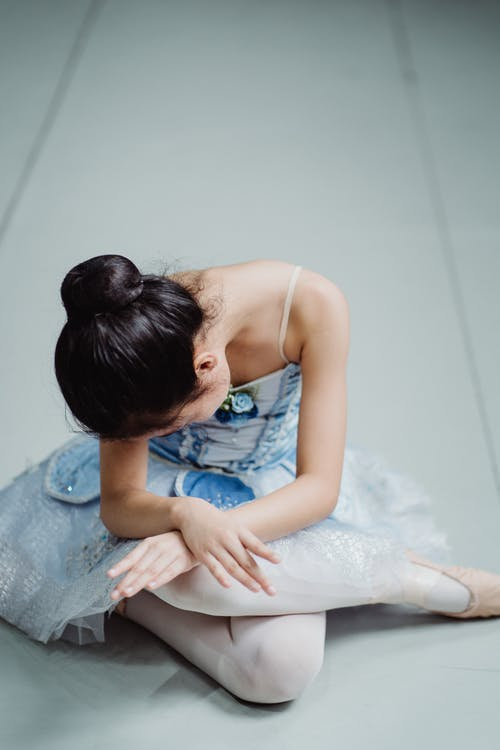 From above full length of unrecognizable girl wearing pointe shoes sitting with legs and arms crossed