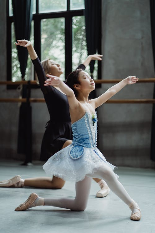 Graceful Asian ballet dancer with girl learning dance