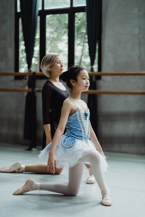 Full body side view of Asian girl wearing pointe shoes and tutu practicing ballet with female instructor in dance hall