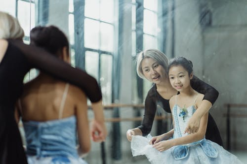 Cheerful Asian female teacher adjusting tutu of student while looking at reflection of big mirror in ballet room with barre