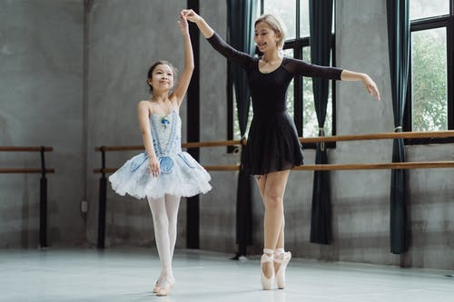 Full body of Asian female teacher wearing pointe shoes and holding hand of student with tutu during lesson in studio with barre
