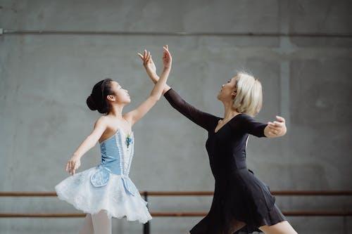 Asian ballet teacher dancing with student