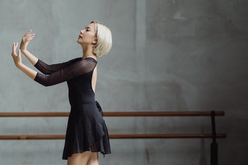 Side view of fit female ballet dancer wearing black tutu and performing dance movement with outstretched arms in ballet class