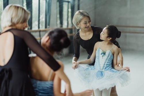 Ballerina with teacher near mirror