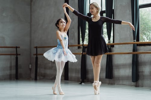 Full body of girl in tutu rehearsing dance while holding hand of teacher in pointe shoes in ballet studio during rehearsal